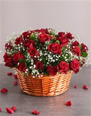 A woven country basket of red roses with greenery