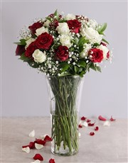 A vase of red and white roses. The arrangement is