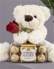 A Dozen red roses in a glass vase, a teddy, a box