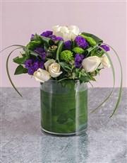 12 cream roses arranged in trio's in a glass vase.